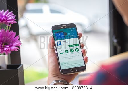 Chiang Mai, Thailand - September 12, 2017: Samsung Galaxy S6 smartphone launches paypal application on the desk screen at the coffee shop.