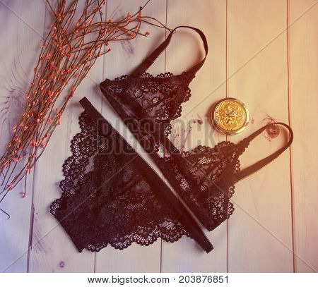 lingerie. women's lacy black underwear with a bust and panties on wooden white background soft focus