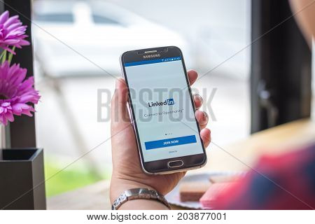 Chiang Mai, Thailand - September 12, 2017: Samsung Galaxy S6 smartphone launches linkedin application on the desk screen at the coffee shop.