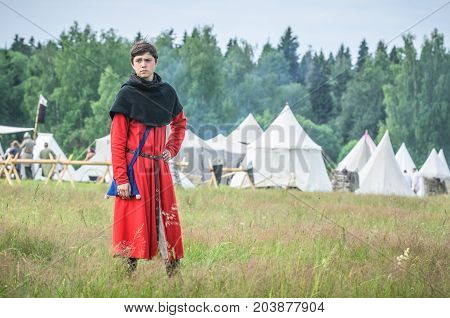 MOSCOW, RUSSIA-June 06, 2016: Man in ancient merchant costume stands on green field of grass.