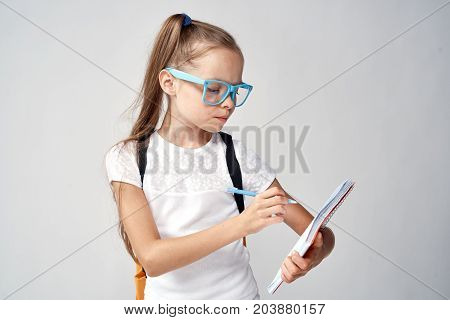 girl in blue glasses writes in notebook.