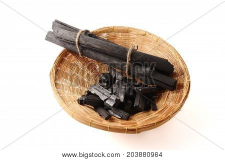Charcoal in basket on a white background.