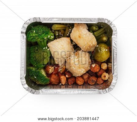 Healthy lunch in foil container. Healthy food take away and delivery. Cuted broccoli, chicken, asparagus, brussel sprout, hazelnuts and sesame in box on white background, closeup, isolated