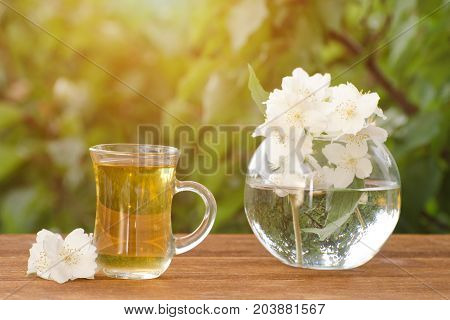 Transparent Mug Of Tea And A Vase With Jasmine On A Wooden Table, Greens On The Background