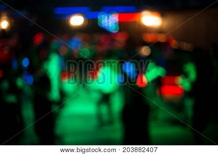 People dance and have a rest in night club. People on blurred background at the party in the night club