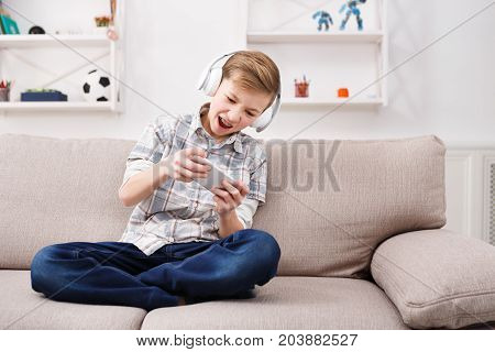 Teenage boy in headphones trying hard to win the game on smartphone. Child wearing braces