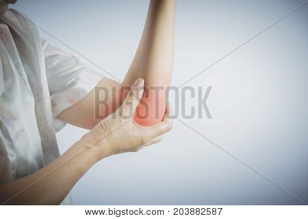 Woman touching her painful elbow. Acute pain in a woman elbow. Female hand holding to spot of elbow pain.