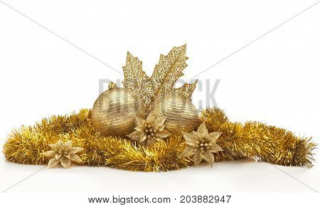 Golden Christmas center piece against white background. Christmas balls golden garland and leaf flowers and spangles.