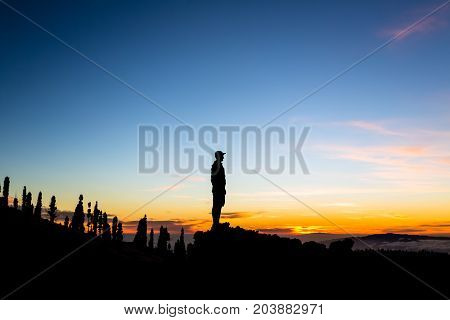 Man celebrating sunset looking at view in mountains. Trail runner hiker or climber reached top of a mountain enjoy inspirational landscape on rocky trail on Tenerife Canary Islands