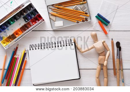 Workplace of artist with copy space. Paints, sketchbook and wooden painter man with brushes on white desk, top view, flat lay, objects