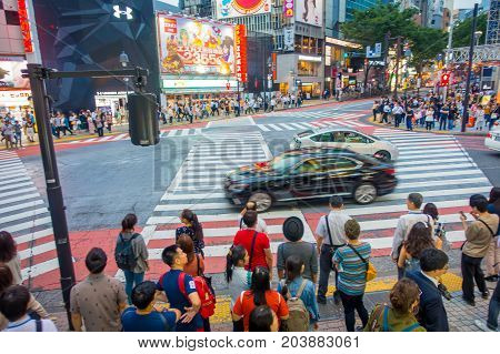 TOKYO, JAPAN JUNE 28 - 2017: Unidentified people waiting the green light for crossing the Shibuya street, while some cars crossing the street in Tokyo, Japan. The famous scramble crosswalk is used by over 2.5 million people daily.