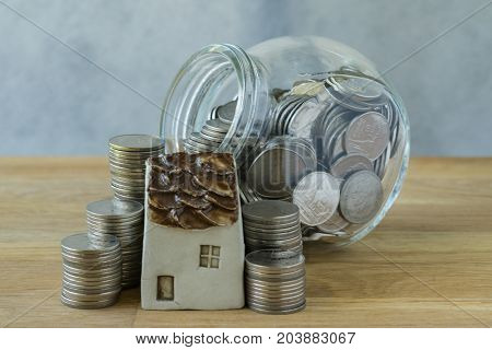 miniature house with stack of coins and coins in glass jar as financial saving or mortgage concept.