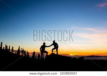 Teamwork couple with helping hand and trust. Silhouette of team help over mountains sunset. Man and woman hikers or climbers reaching goals in inspirational landscape on Tenerife Canary Islands.