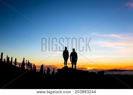 Teamwork couple climbing and reaching mountain peak. Silhouette of climbers team over mountains sunset. Man and woman hikers looking at inspirational landscape on Tenerife Canary Islands.