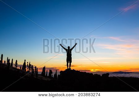 Man celebrating sunset with arms outstretched in mountains. Trail runner hiker or climber with hands raised reached top of a mountain enjoy inspirational landscape on Tenerife Canary Islands