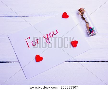 white envelope with an inscription for you on a white wooden background