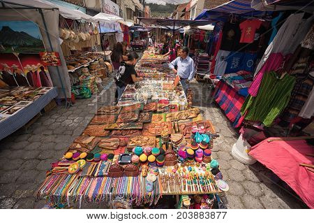 April 29 2017 Otavalo Ecuador: indigenous quechua people selling artisan gifts on stands set up on the street in the Saturday market