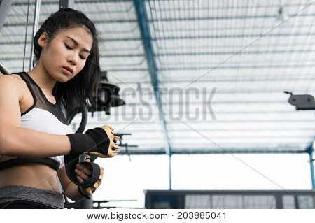 young woman wearing gloves in fitness center. female athlete prepare for training in gym. sporty girl ready for working out in health club.