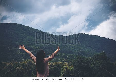 A woman turn back and stretched the arms with blue sky green nature and mountain background
