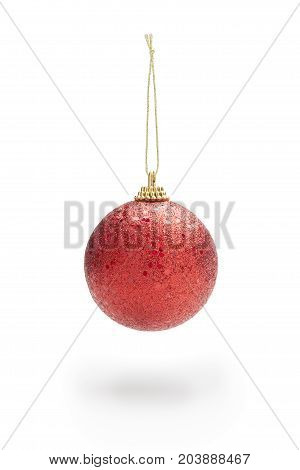Glowing red color christmas ball hanging from cord. Soft shadow against white background. Clipping path