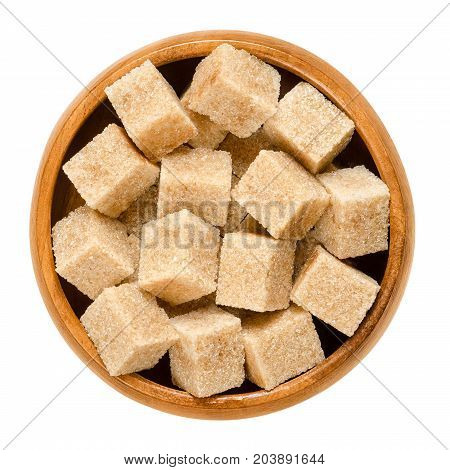 Demerara brown sugar cubes in wooden bowl. Also called sugar lumbs. Sucrose sugar product with distinctive brown color due to the presence of molasses. Macro food photo close up from above over white.