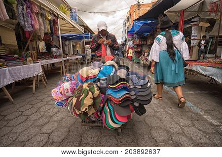 April 29 2017 Otavalo Ecuador: mobile vendor selling hats from a cart in the Saturday market