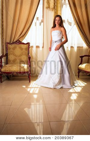 Bride with long loose hair standing in a richly decorated room in a pool of natural light