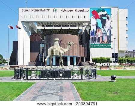 Dubai, United Arab Emirates - July 5, 2004: Exterior view of the Municipality Building on the Creek side with a camel statue in front.