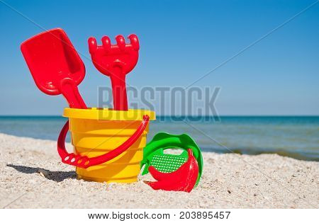 Yellow baby bucket with a red handle, plastic red spatula and rake, and green sieve, a red sand form in the form of a banana, blue sea and sky, yellow sand beach shore sea shells summer vacation sunny