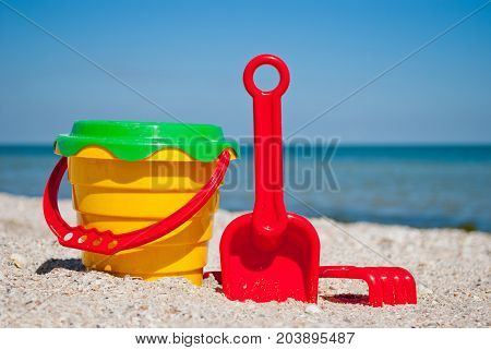 Yellow childrens bucket with red handle, plastic red spatula and rake, green sieve, blue sea and sky yellow sand beach sea shore seashells summer vacation sunny summer day, bright sun, children's toys