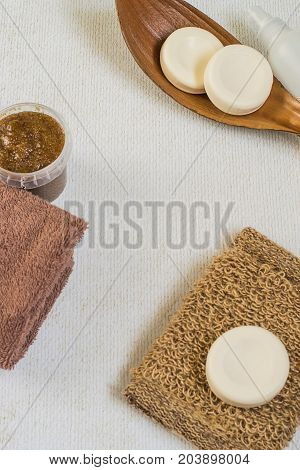 Skin care products. Round pieces of soap a jar with a cosmetic body scrub loofah and terry towels on a light background.