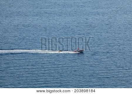 PLATAMON GREECE - 28 JULY 2016: Inflatable donutboats being pulled by a speedboat shoot from high distance and from above near to Platamonas or Platamon Greece Olympic region