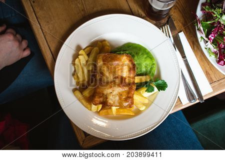 A Traditional British Plate Of Fish And Chips With Mushy Peas On A Diner Table