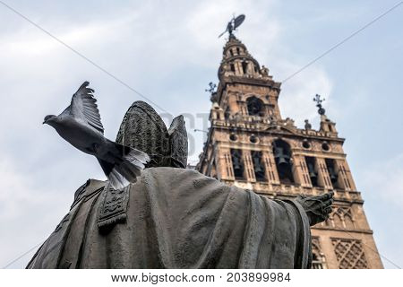 Statue opposite to the weather vane of Seville, pigeon initiates the flight, Andalusia, Spain, conceptual image