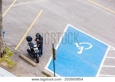 Ile D'Orleans Canada - June 1 2017: Aerial view of biker man by motorcycle in parking lot with disabled blue spot at rest stop by highway road