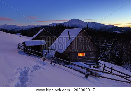 A trodden path leads to the wooden house in the snow on the background of beautiful snow-capped mountains.