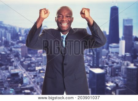 Cheering african american businessman with skyline with skyline of city in background