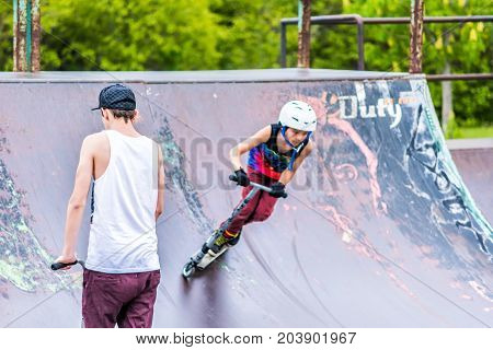Saguenay Canada - June 3 2017: Downtown city summer park in Quebec with young teenagers boys skating performing tricks stunts on scooter on metal rusty playground ramp skatepark