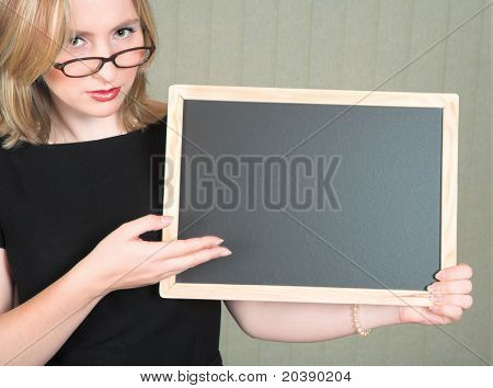 Young serious blond woman teacher in black dress and pearls, wearing glasses pointing at empty blackboard