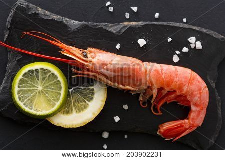 Boiled shrimp with salt and lemon on black background, close up. Top view on appetizing seafood snack, restaurant serving.