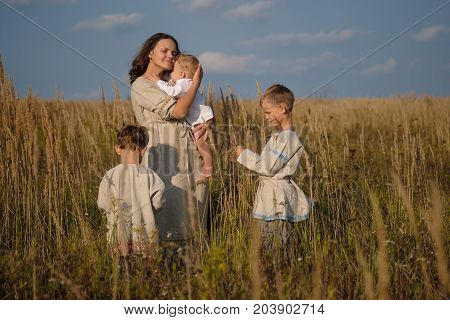 mom and three sons of European appearance among the tall grass in the field