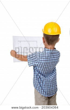 Young serious builder reading a construction plan, turned back, isolated on white background