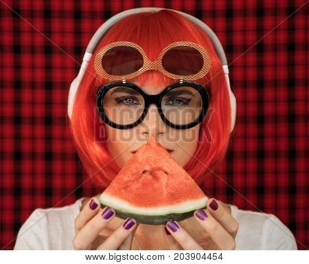 A fashionable woman in a red wig and glasses, listening to music in white headphones and holding a piece of ripe watermelon. Summer image of a modern teenage girl.