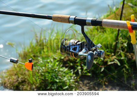 Tackles for fishing: rod with a coil. Fishing on the river bank in the summer morning.