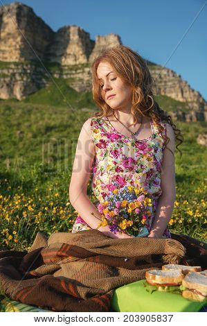 A beautiful fair-haired bride sits on a plaid plaid at the cliff with a bouquet in her hands and waits for her slob