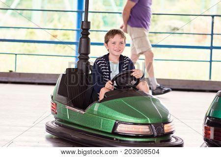 Happy Child Boy Having Fun In Amusement Park