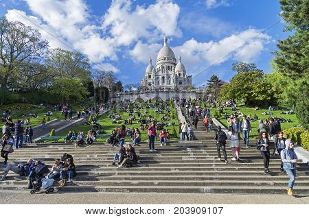 Tourists On The Hillside Of Montmartre On The Background Of The Sacre-coeur Basilica.