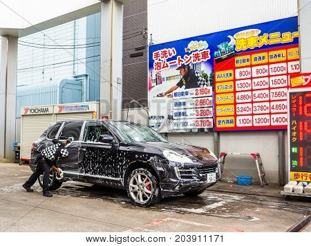 YUFUIN, JAPAN JUNE 28 - 2017: Close view of a car wash with a man cleaning a black car at station Yufuin village where is the destination of tourist for looking the local village in Japanese style