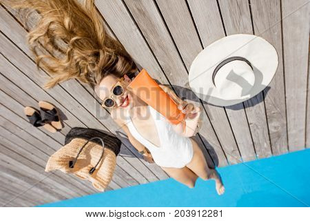 Woman in swimsuit showing a tube with sunscreen lotion lying near the basin outdoors. Sunscreen solar cream uv protection concept
