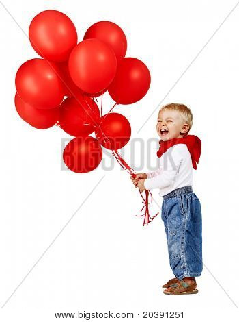 cute little boy in white shirt, jeans and red scarf laughing as he holds a bunch of red balloons.